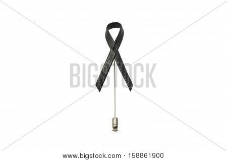 Brooch black ribbon leather on white background . melanoma awareness. Mourning symbol.