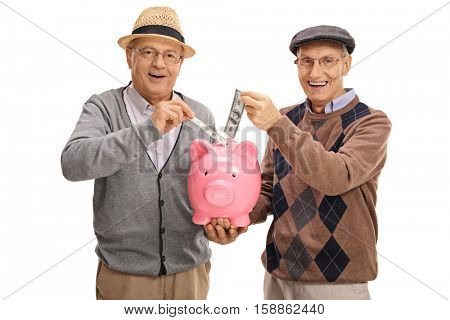 Seniors putting money in a piggybank and looking at the camera isolated on white background