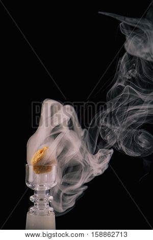Marijuana extraction concentrate aka wax crumble on a glass rig with smoke isolated on black background
