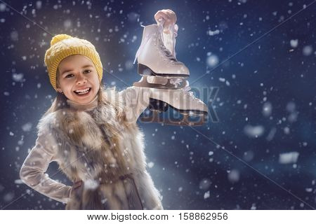Happy child girl playing on a snowy winter walk. Little girl enjoys the game. Child girl playing outdoors in snow. Outdoor fun for winter vacation. Portrait kid with skates on dark background.