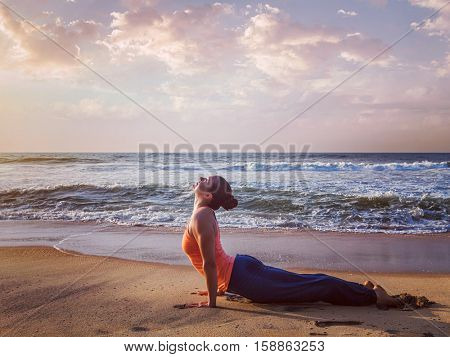 Vintage retro effect hipster style image of Yoga outdoors on beach - woman practices Ashtanga Vinyasa yoga Surya Namaskar Sun Salutation asana Urdhva Mukha Svanasana - upward facing dog pose on sunset