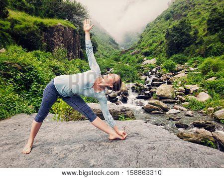 Woman doing Ashtanga Vinyasa yoga asana Utthita trikonasana - extended triangle pose outdoors at waterfall in Himalayas. Vintage retro effect filtered hipster style image.