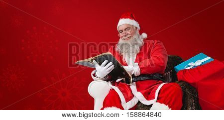 Santa reading bible with sack of Christmas present beside him against red snowflake background