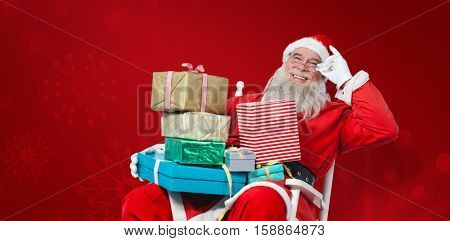 Cheerful Santa Claus holding Chritmas presents while sitting on chair against red snowflake background