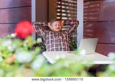 The man sitting in the cafe at the table and looking at a laptop. The guy in a checkered shirt hipster with a beard looking at the screen. Leaning back in his chair with his hands on his head man watching computer