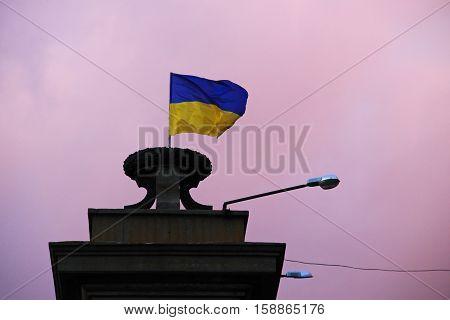Flag of Ukraine against sky at sunset