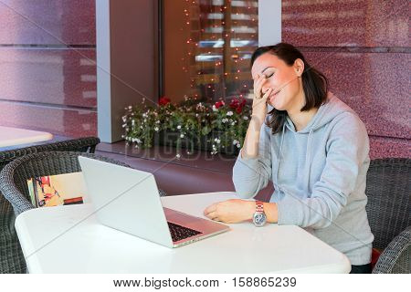 Girl in a cafe using a laptop a wireless Internet connection. The hand covers her face funny and shy expression on her face