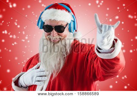 Santa claus showing horn sign while listening to music on headphones against white light dots on red