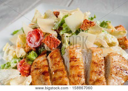 Fried chicken strips with fresh vegetable salad close-up. Served caesar on white plate. Mediterranean cuisine, restaurant menu, appetizing concept