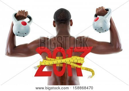 Rear view of shirtless fit man lifting kettle bells against digitally generated image of new year with tape measure