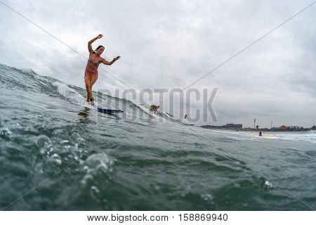 BALI, CANGGU - NOVEMBER 25 2016: Young lady surfer catching the wave in the ocean