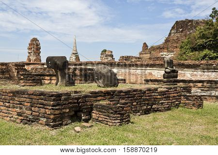 Ruins of the red brick temple of Wat Mahathat the Temple of the Great Relic and the remains of some headless Buddha statues in Ayutthaya Thailand