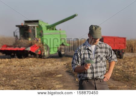 Farmer holding Euro banknote with combine harvester in background serious face corn harvest concept