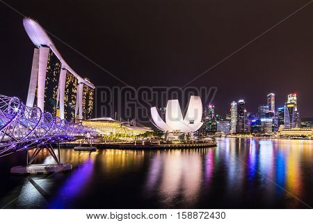 Singapore - June 24, 2016: Singapore city skyline at night. Helix bridge, Marina Bay Sands hotel and business district