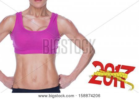 Female bodybuilder posing in pink sports bra and shorts mid section against digitally generated image of 3D new year with tape measure