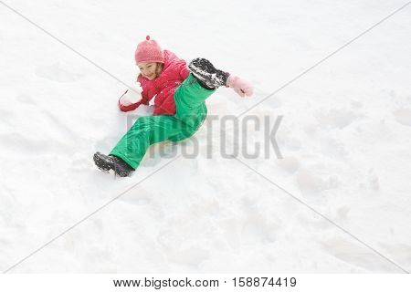 Playful girl with braids playing in snow having fun and being active. Natural lifestyle and free childhood concept with copy space.