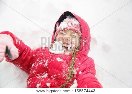 Playful girl with braids having fun in the first snow playing in it throwing it in the air and being active. Natural lifestyle and free childhood concept with copy space.