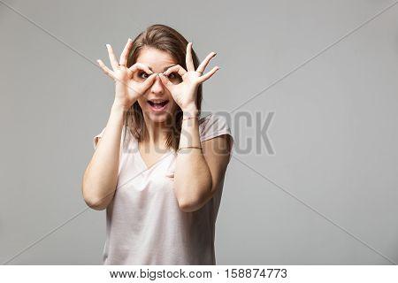 Portrait of brunette woman showing ok sign on eyes.