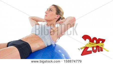 Fit woman doing sit ups on blue exercise ball against digital image of 3D new year with tape measure