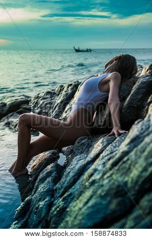 Pretty blonde woman in sexy white swimsuit leaning against rocks over beautiful sea and sunset sky background