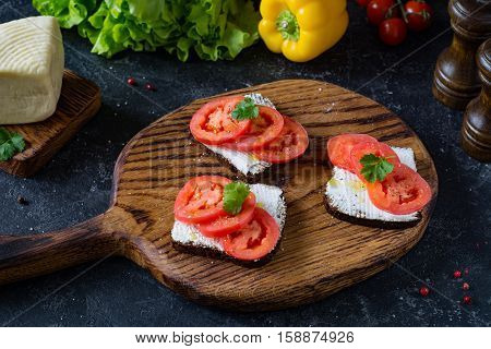 Healthy sandwhiches with fresh ricotta cheese, tomatoes and parsley on whole grain rye bread. Side view, front focus