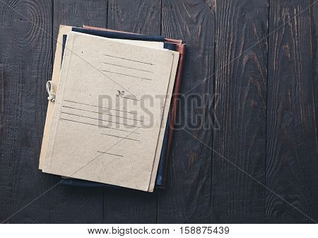 stack of retro folders on old wooden background