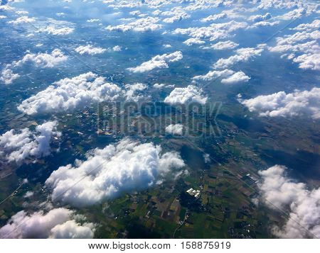 A wide-angle aerial view of multiple cumulus clouds over farmland Tak province Thailand.