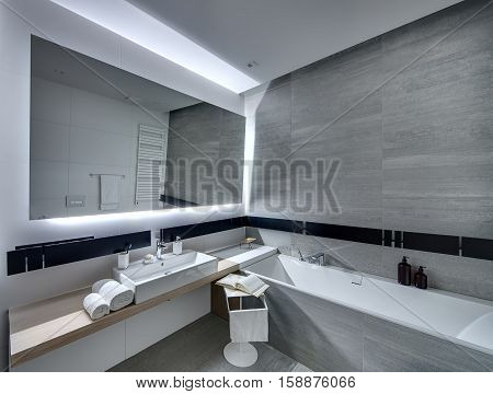 Contemporary bathroom tiled with the white and gray tiles. There is a white sink with accessories, big mirror, bath, towel holder, towel radiator, white stand with a towel and a book. Horizontal.