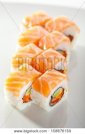 Maki Sushi with Fresh Salmon and Vegetable inside. Topped with Salmon