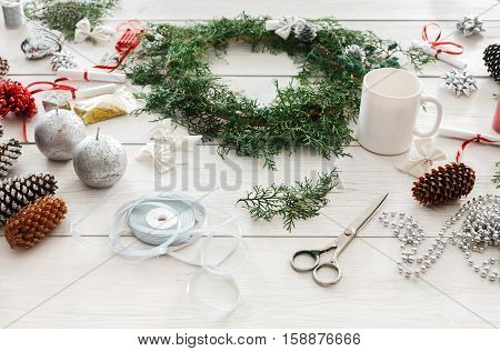 Creative diy craft hobby. Making handmade craft christmas ornaments and thuja tree garland. Home leisure, tools, trinkets and pine cones for holiday decorations. View of white wooden table