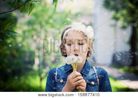 Young Girl with light hair Blowing a Dandelion Outdoors