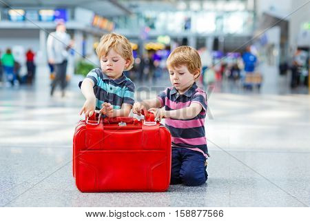 Two little kid boys with suitcases at the airport, indoors and waiting for going on family vacations. Happy children, twins and brothers about exciting air travel trip and flying with airplane.