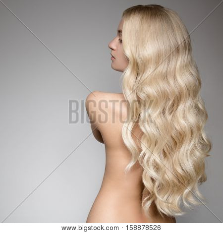 Portrait Of A Beautiful Young Blond Woman With Long Wavy Hair. Back View