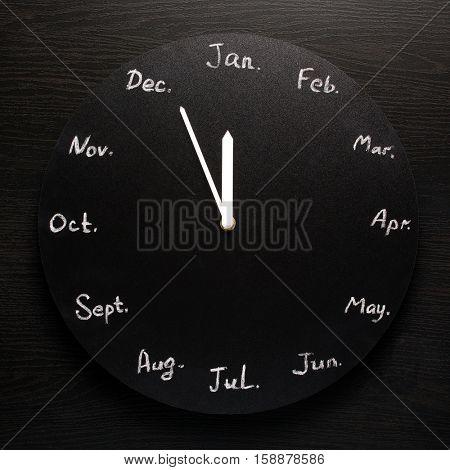 Black round clock calendar. 12 months