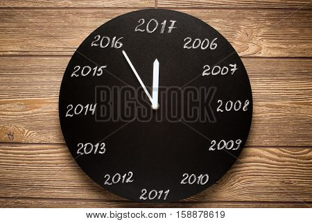 Concept of clock on the eve of 2017. Wooden background.