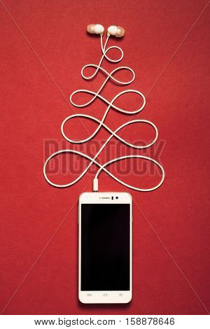 Concept. Christmas tree from smartphone and headphones. Happy new year.