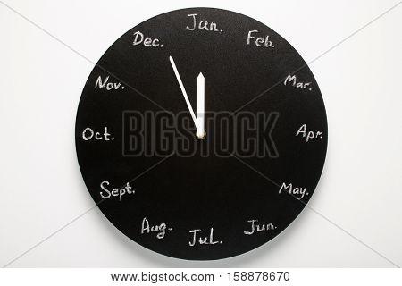 Black round clock calendar. 12 months. White background