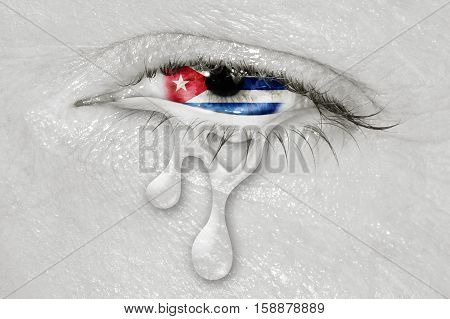 Crying eye with Cuba Flag iris on black and white face. concept of sadness for Cuba, patriotic metaphor.