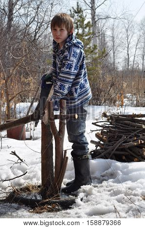 The teenage boy saws a hacksaw dry branches on the seasonal dacha