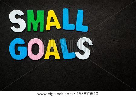"""Colorful wooden letters forming the phrase """"small goals"""""""