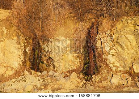 Small waterfalls in the stone quarry on autumn