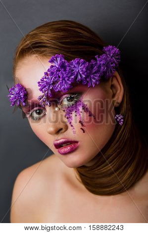 Fashion portrait beautiful woman with fabulous make-up lilac flowers on the face. The idea of creative and original make-up for make-up artists.