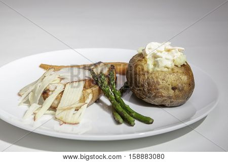 A baked potato with pork loin and shredded apple. Served with sauteed asparagus carrots and chunky coleslaw.
