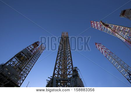 Oil rig legs high up and sky blue. View from below.