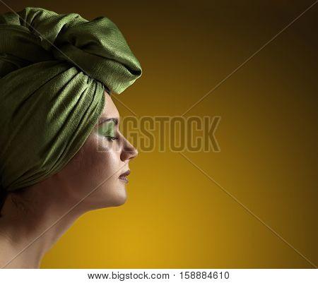 Woman In  Green Turban On Yellow Background