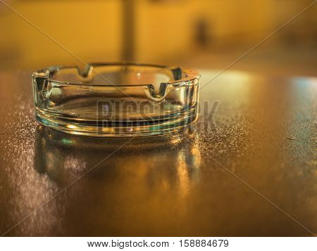 Picture of the glassy ashtray close up. Ashtray laying on the blurred surface of the table. Blurred background of the ashtray on the table. Blurred surface of the table reflects yellow sunlight.