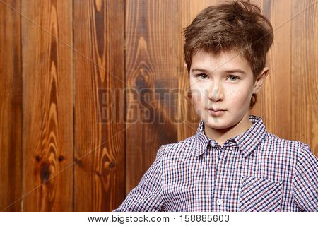 Portrait of a cute nine year old boy posing at studio over wooden wall background. Kid's fashion. Clothes for children.