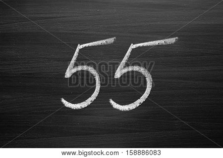 number fifty five enumeration written with a chalk on the blackboard