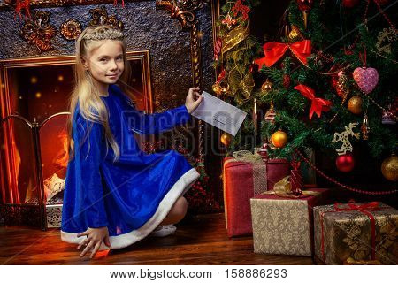 Beautiful eight year old girl in a blue dress and a tiara like a Snow Maiden standing near the Christmas tree. Beautiful Christmas decoration.