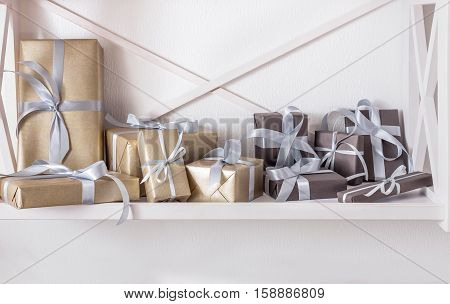 Elegant gift boxes wrapped in paper on white shelves in modern interior. Any holiday background with copy space. Christmas, birthday or valentine concept. High key